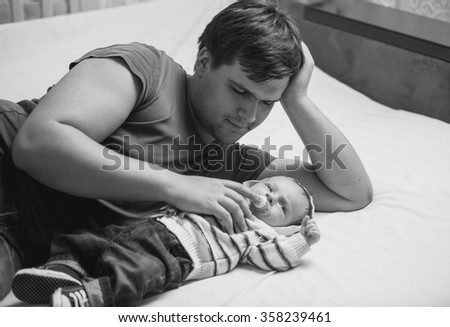 Black and white portrait of young father lying on bed with his newborn baby - stock photo