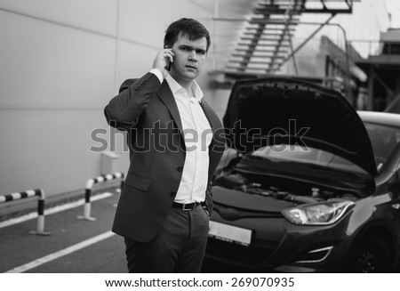 Black and white portrait of young man calling by phone to car service - stock photo