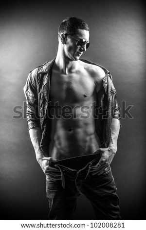 Black and white portrait of young man posing with naked torso - stock photo