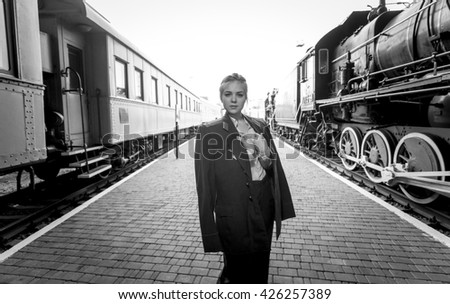 Black and white portrait of young woman in uniform on railroad platform - stock photo