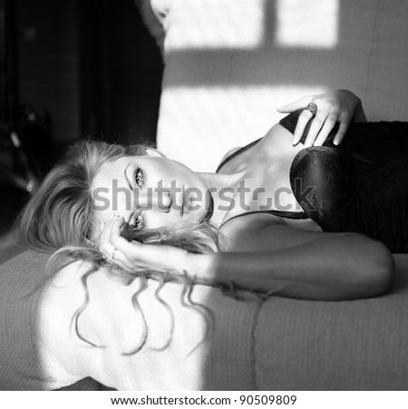 black and white portrait of young woman lying upon a sofa - stock photo