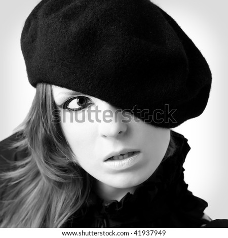 Black and white portrait of young woman wearing beret - stock photo