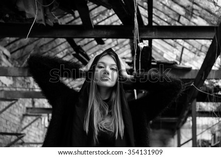 Black and white portrait of young woman, with blond long hair, wearing on black jacket with scarf on her head, posing on the old building background and looking at camera, waist up