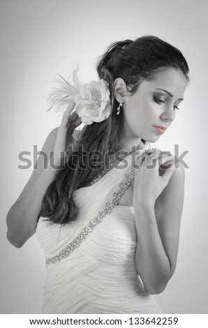 black and white portrait with one color of bride in wedding dress who holding a flover with one hand and the other hand on the shoulder