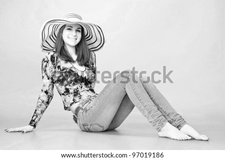 Black and white portrait. Young beautiful  long haired woman wearing a hat and jeans, sitting on the floor. Vintage style
