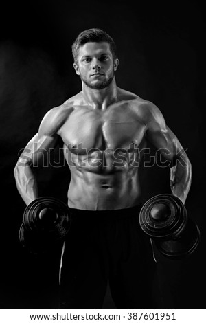 Black and white, Portraying masculinity. Cropped shot of a ripped fitness man working out with dumbbells showing off his muscles