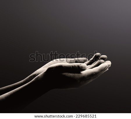 Black and white poverty children open empty spiritual hands with palms up. Human hands of prayer over light in dark room background. Pray for support, Person hands begging for food or help concept. - stock photo