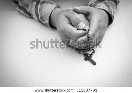 Black and white, prayer man hand with rosary - stock photo