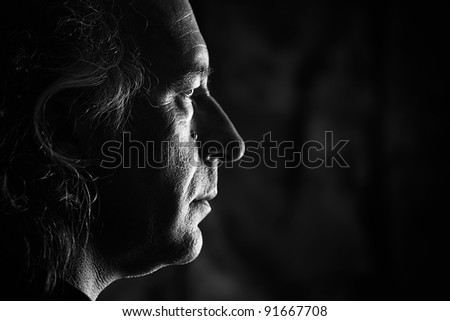Black and white profile portrait of older white male with side lighting. - stock photo