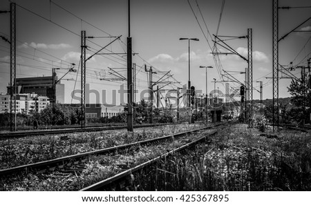 Black and white railway in landscape orientation with few buildings on the left side - stock photo