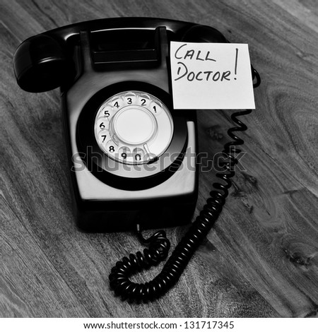 Black and white retro telephone with reminder note - stock photo