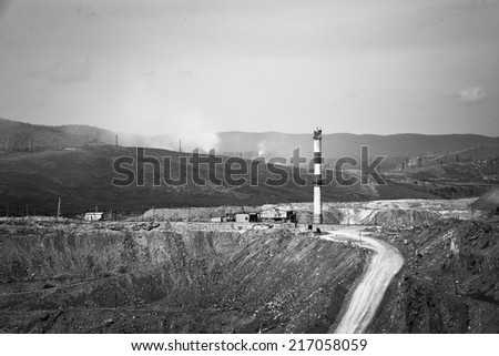 Black-and-white road, factory on top and hill - stock photo