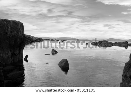 black and white scenic view in kerry ireland of rocks and sea with mountains against a beautiful blue cloudy sky - stock photo