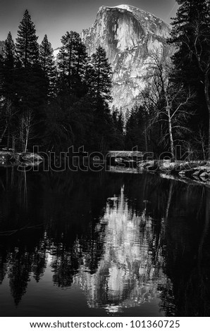 Black and white scenic view of snow capped mountain and forest reflected on lake. - stock photo
