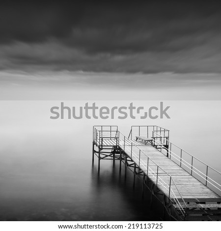Black and white seascape shot.  Old wooden pier with steps to the sea. Daytime long exposure. Odessa, Ukraine. - stock photo