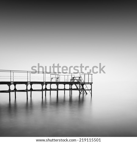 Black and white seascape shot.  Old wooden pier with steps to the sea. Daytime long exposure. Odessa, Ukraine - stock photo
