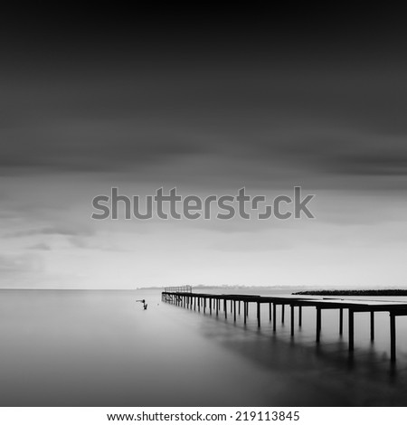Black and white seascape with old metal pier in the sea and beautiful sky, Black sea, Odessa, Ukraine - stock photo