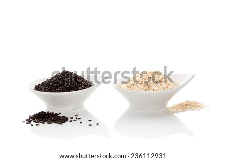 Black and white sesame seeds isolated on white background. Culinary healthy food ingredient. - stock photo