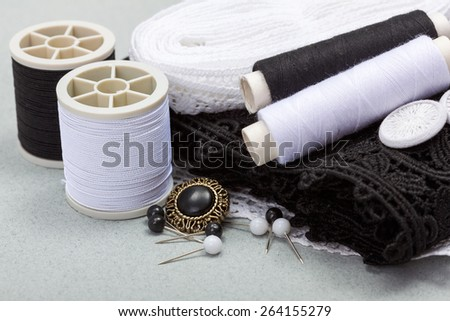 Black and white sewing kit: buttons, push pins, threads and materials - stock photo