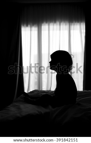 black and white shadow figure of a little boy near the window