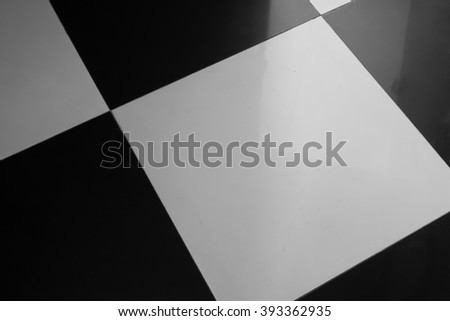 Black and white shiny tiles with door's shadow reflection - floor pattern - stock photo