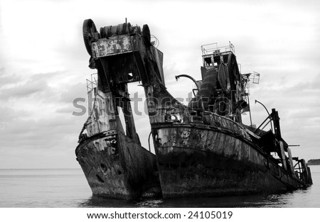 Black and white ship wreck - formally a dredge. - stock photo