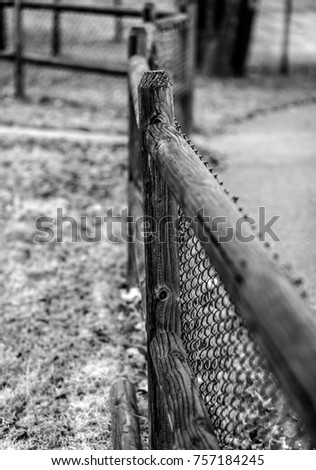 black and white shot of a chain link fence with wooden frame with one fence
