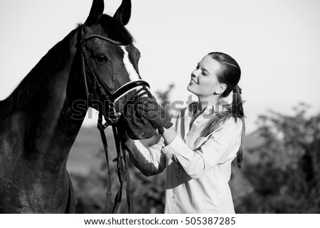 Black and white shot of a smiling young woman taking care of her bay horse.
