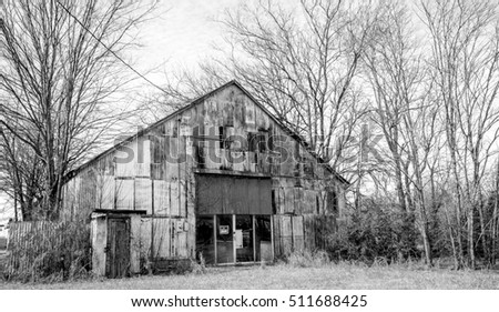 Black and white shot of an old abandoned and neglected building sitting in a field of dry grass and bare trees.