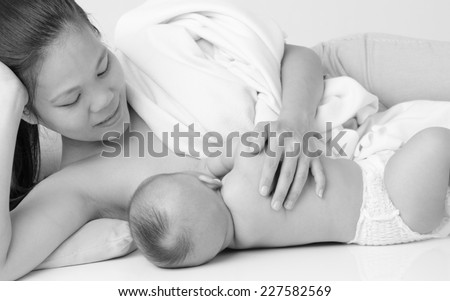 Black and white shot of asian woman breastfeeding her baby