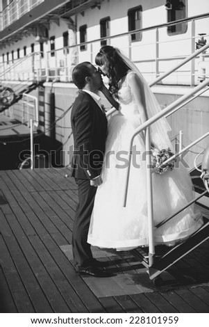 Black and white shot of bride and groom kissing on pier against cruise ship - stock photo