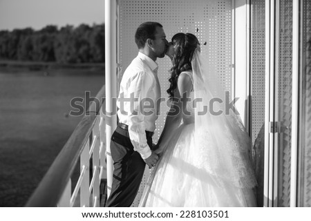 Black and white shot of bride and groom kissing on ship deck - stock photo