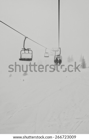 black and white shot of chairlift and skiers in the winter - stock photo