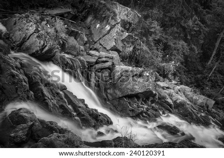 black and white shot of the waterfall streams - stock photo