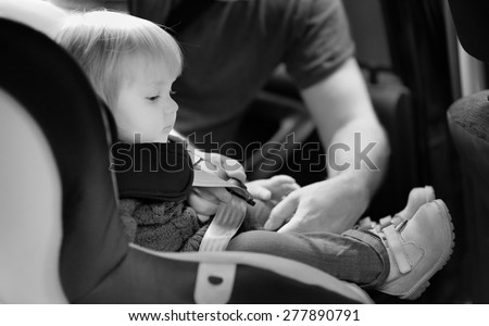 Black and white shot of toddler boy in the car seat - stock photo