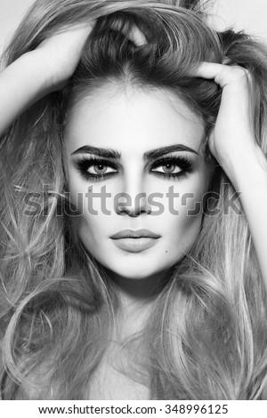 Black and white shot of young beautiful sexy girl with long hair and smoky eyes - stock photo