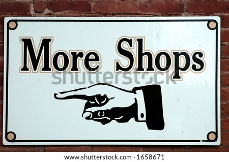 black and white sign with hand pointing left for More Shops - stock photo