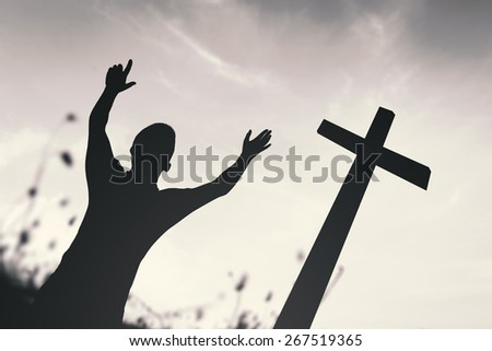 Black and white silhouette human raising hands over the cross on nature background. - stock photo