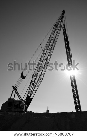 Black and white silhouette of crane-mounted pile driver on construction job site