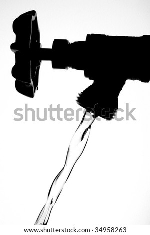 Black and white silhouette of faucet with running water. - stock photo