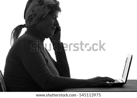 black and white silhouette of grandmother talking on the phone and working on computer at home