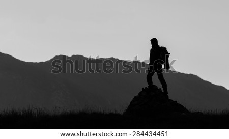 Black and white silhouette of hiker on the top of the hill. Lifestyle concept