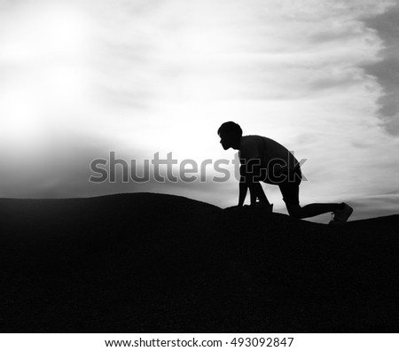 Black And White Silhouette Of Man Climbing Mountain With Dramatic Sky Clouds