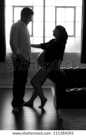 Black and white silhouette of pregnant woman reaching out for her husband.