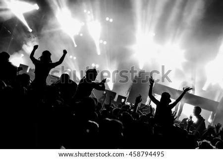 Black and White Silhouette People on Shoulders in Crowd at a Music Festival - Backlit.