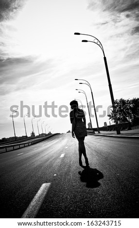 Black and white silhouette photo of woman walking on empty highway - stock photo