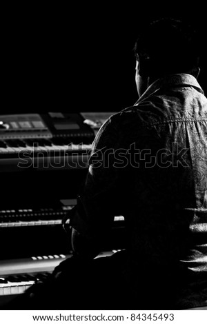 Black and white silhouette portrait of a keyboard player playing 3 keyboards. - stock photo
