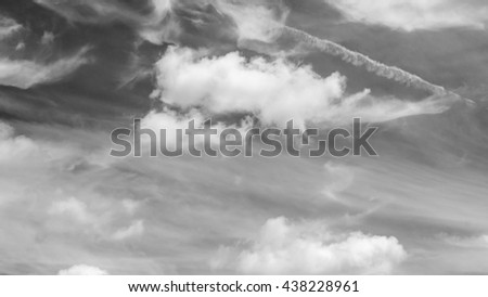 black and white sky with vapor trails from a plane,black and white clouds - stock photo