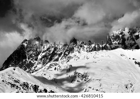 Black and white snowy rocks in haze at sunny day. Caucasus Mountains. Svaneti region of Georgia. - stock photo