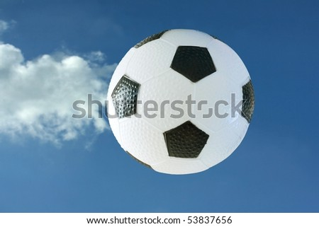 Black and white soccer ball against a blue sky - stock photo